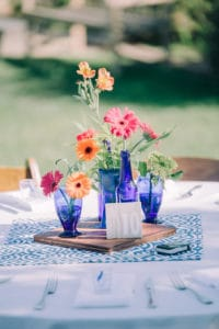 bright orange and pink flowers in clear blue vases