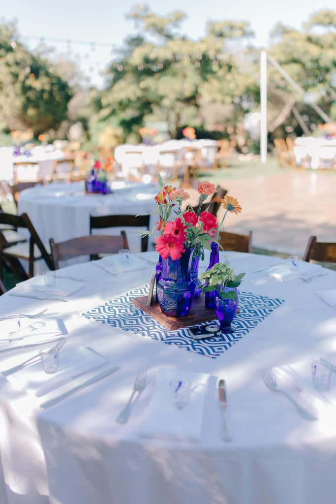 blue bottles with bright flowers as centerpiece