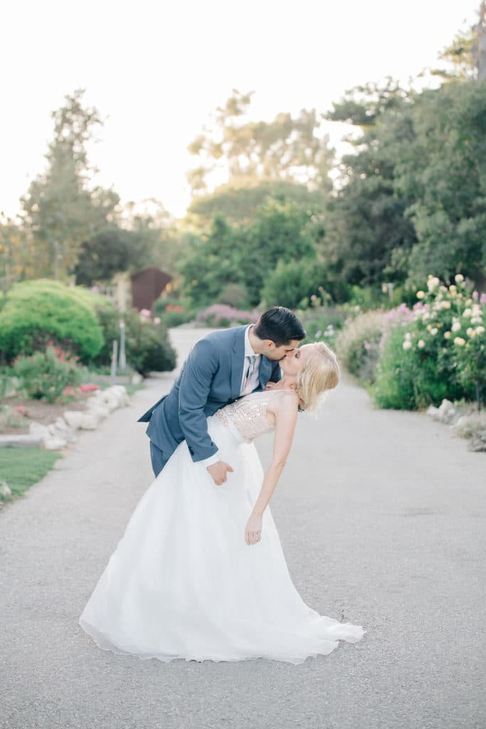 bride and groom dip kiss with fairytale ballgown in garden
