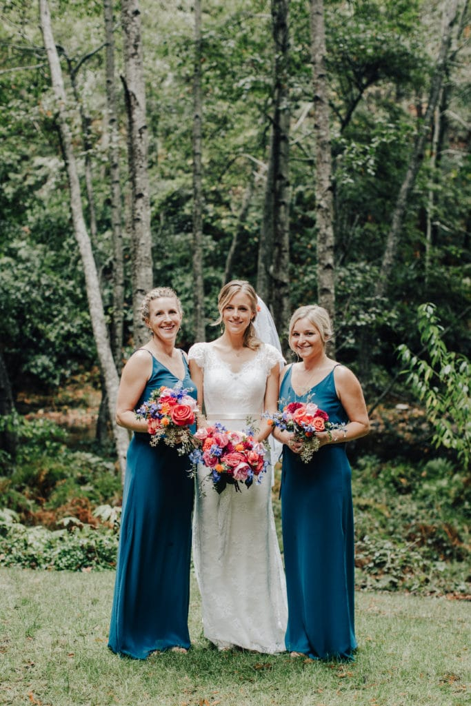 bride and bridesmaids in jewel tone dresses in woods
