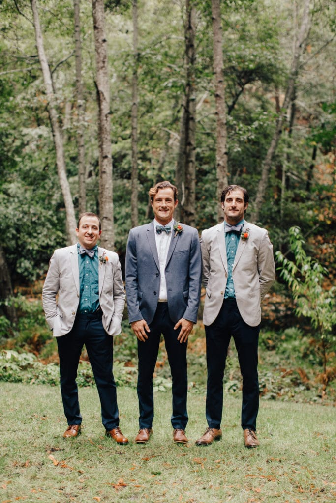 groom and groomsmen in the woods with teal shirts