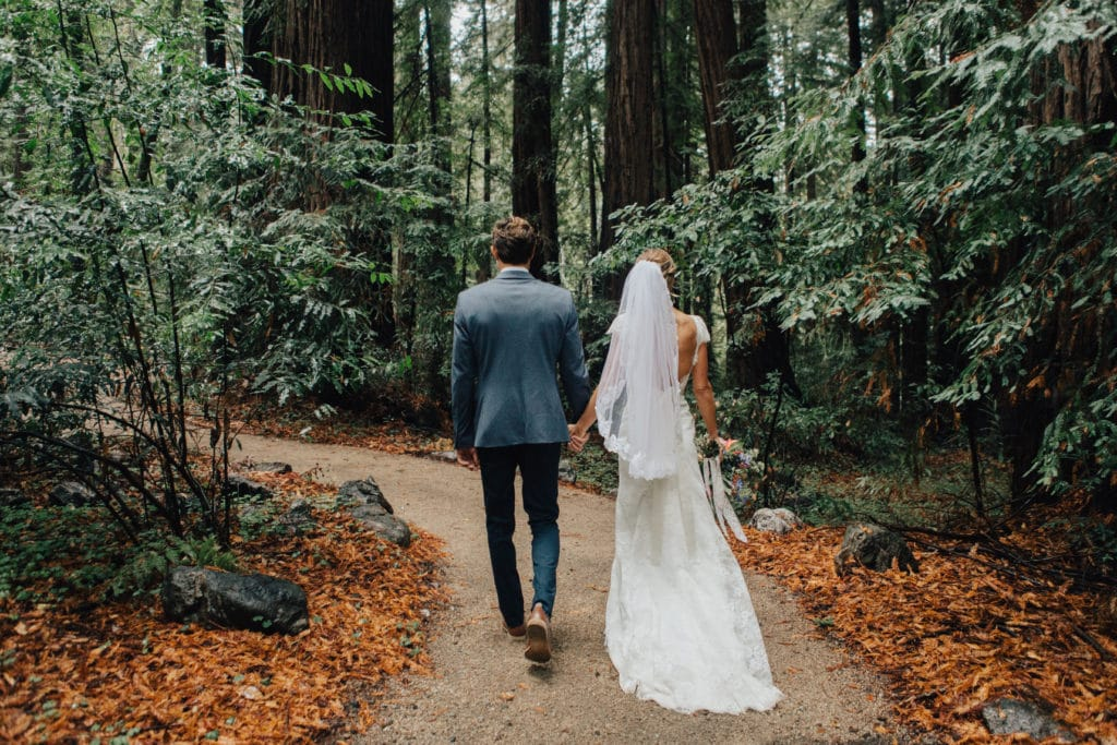 bride and groom walk during fall wedding in big sur woods