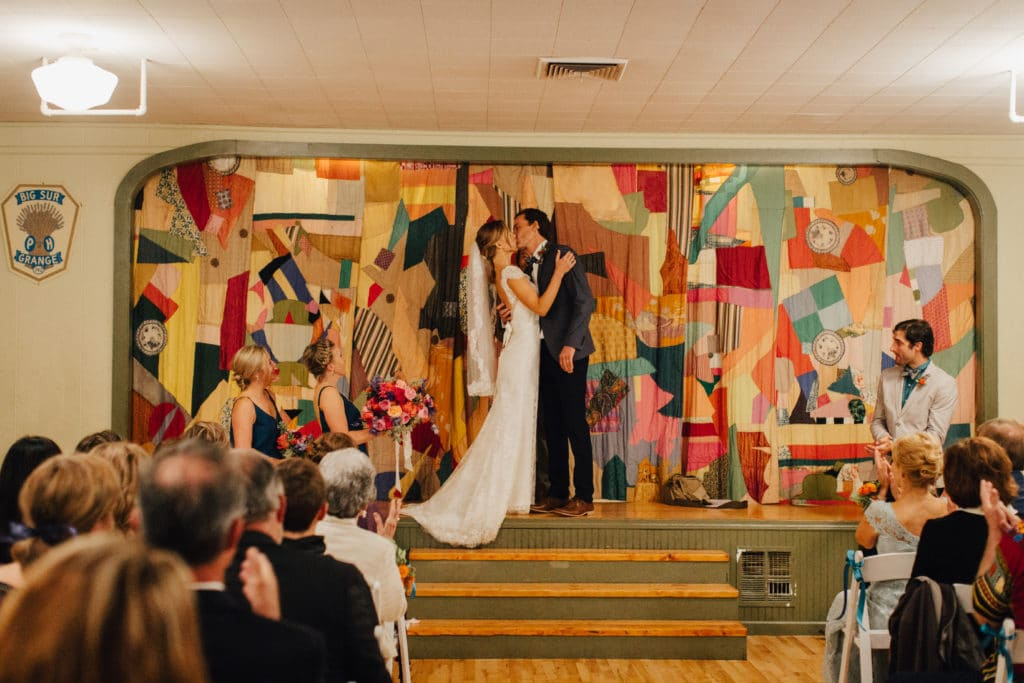 bride and groom kiss in front of colorful curtain big sur hall