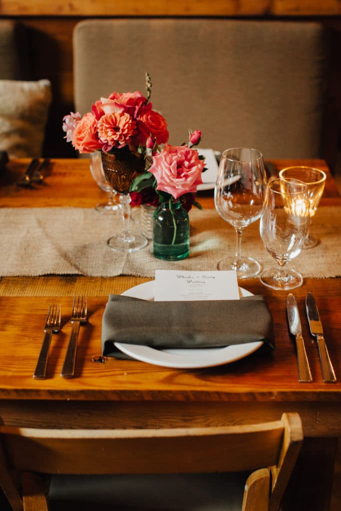 bud vases and on wooden tables with black napkins at ventana inn wedding
