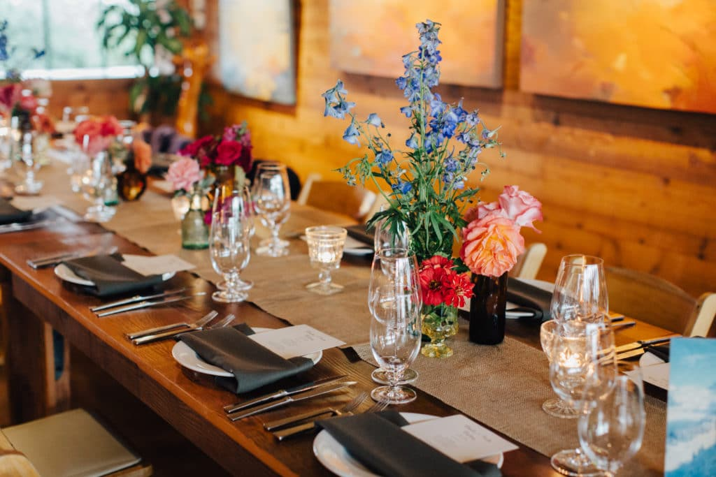family style wedding tables with bright florals and black napkins