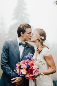 bride and groom kiss with foggy air. bow tie and bright bouquet