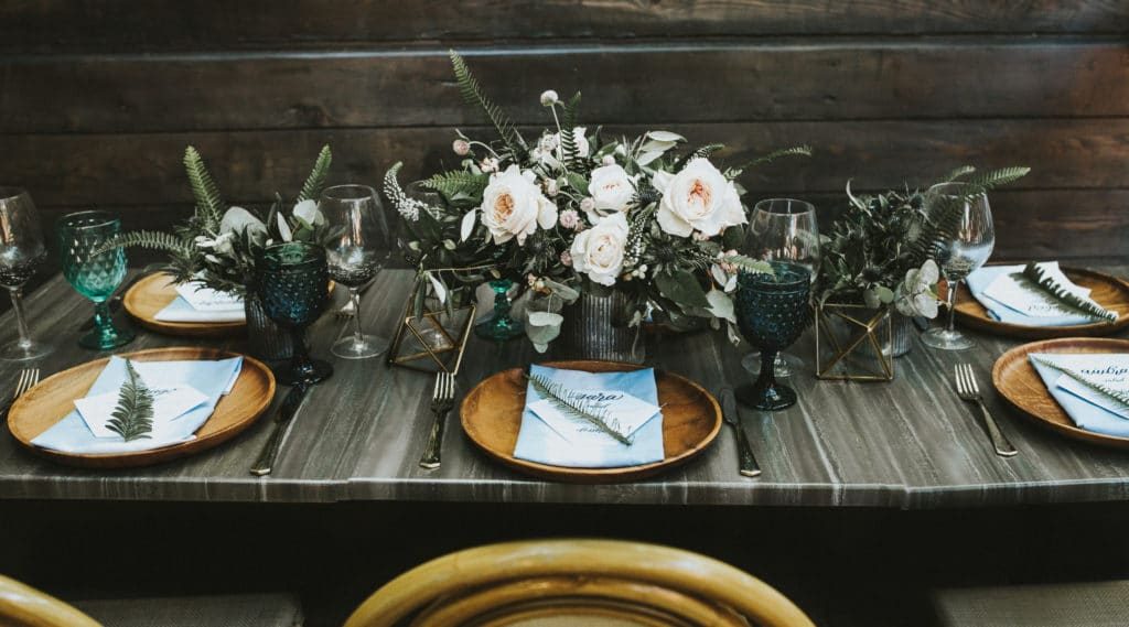 moody tablescape for eco-friendly wedding with ferns and wooden plates