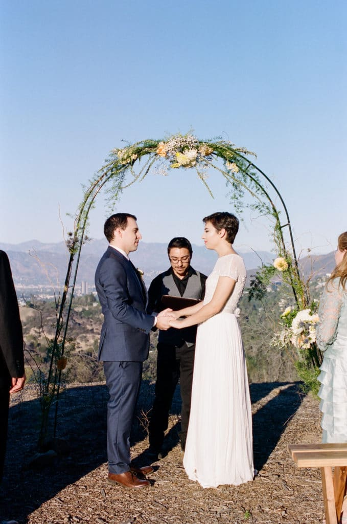 bride and groom under simple arch at treepeople park overlooking los angeles