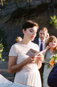 Bride and short hair and bright lip saying vows at treepeople park