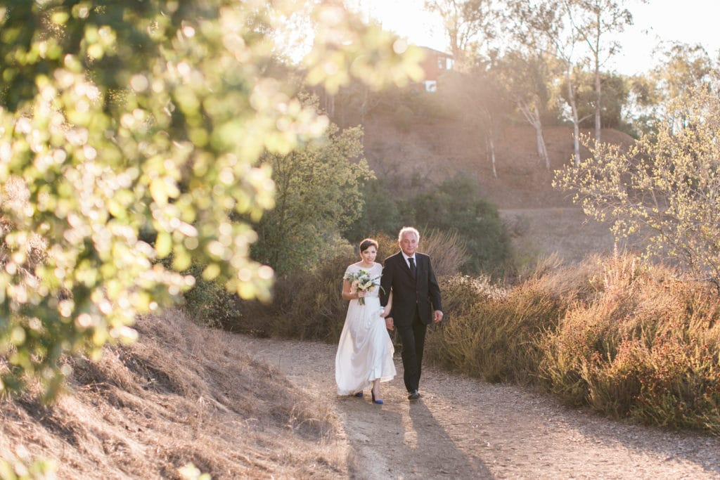 Bride and father walk down the path at TreePeople Park for the ceremony overlooking Los Angeles