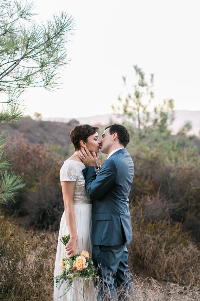 adventurous couple kiss on top of a mountain in Los Angeles. Boho bride with soft bouquet