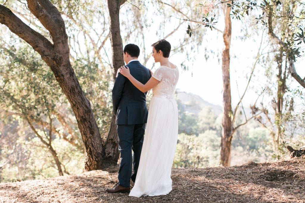 Bride taps groom on shoulder for first look at Tree People park. A great wedding venue in Los Angeles in the Santa Monica Mountains