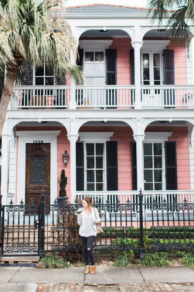 Gabrielle Norton posing in front of pink house in New Orleans with green smoothie