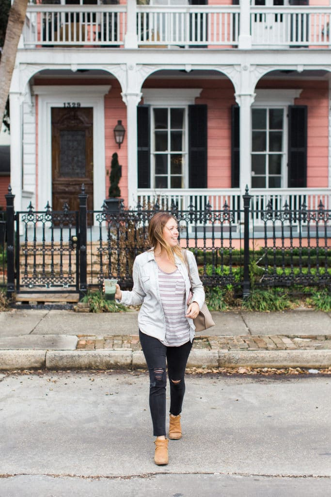 Pink house in New Orleans girl crossing street with green juice and Coach purse
