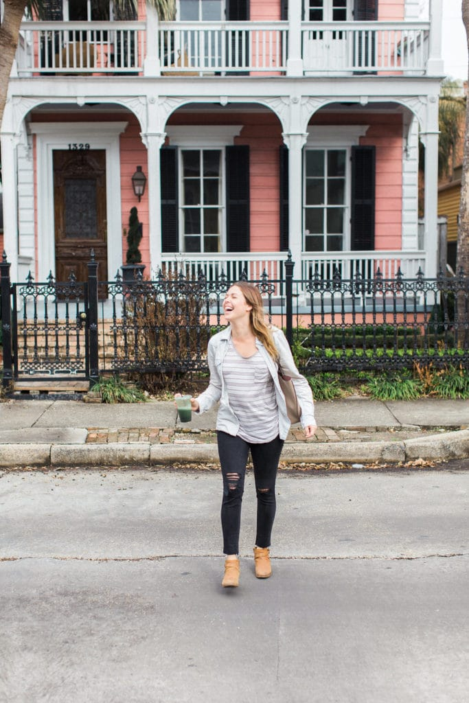 Pink house in New Orleans and wedding planner with green smoothie in front