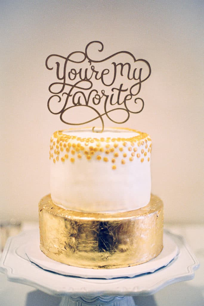 gold and white cake with You're My Favorite cake topper