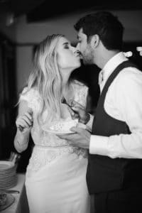 bride and groom kiss after cake cutting