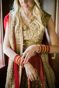 bride in red and gold lehenga with red and gold bracelets for indian fusion wedding