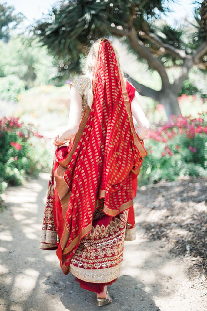back of lehenga red and gold on blond american bride