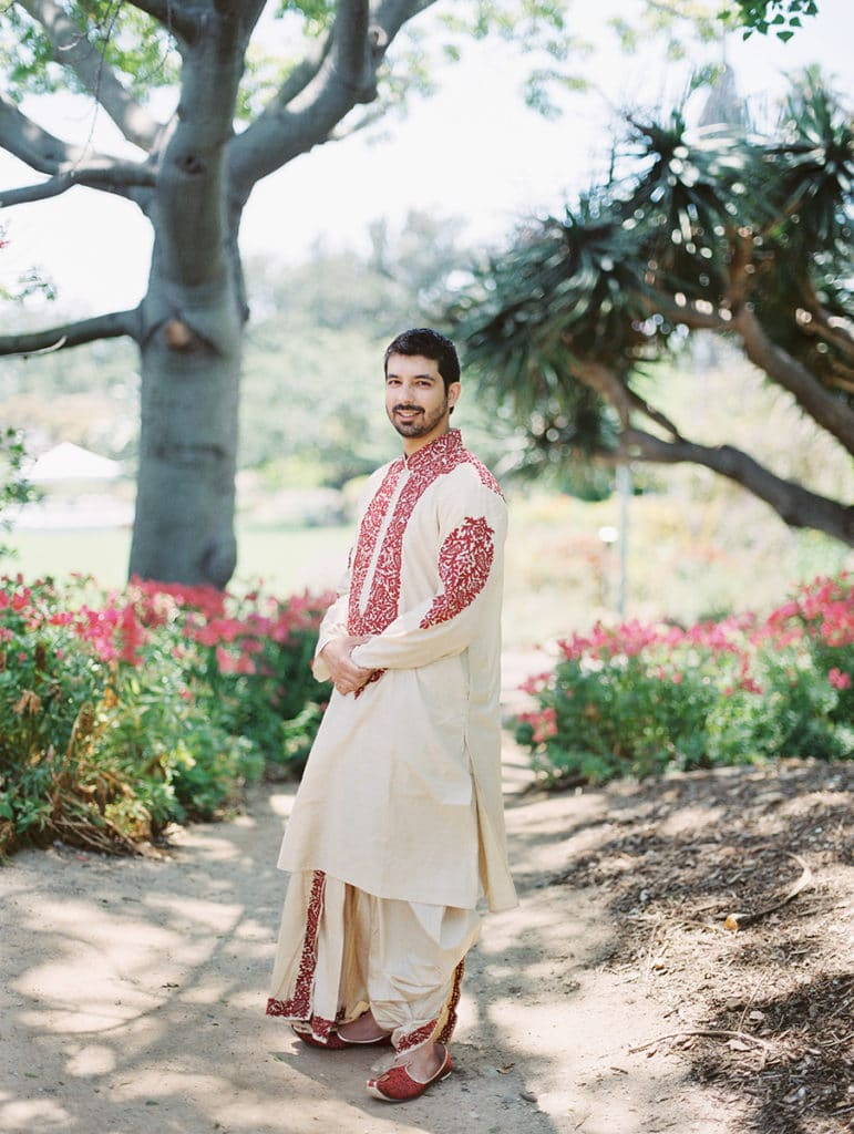 indian groom before hindu ceremony red and white outfit