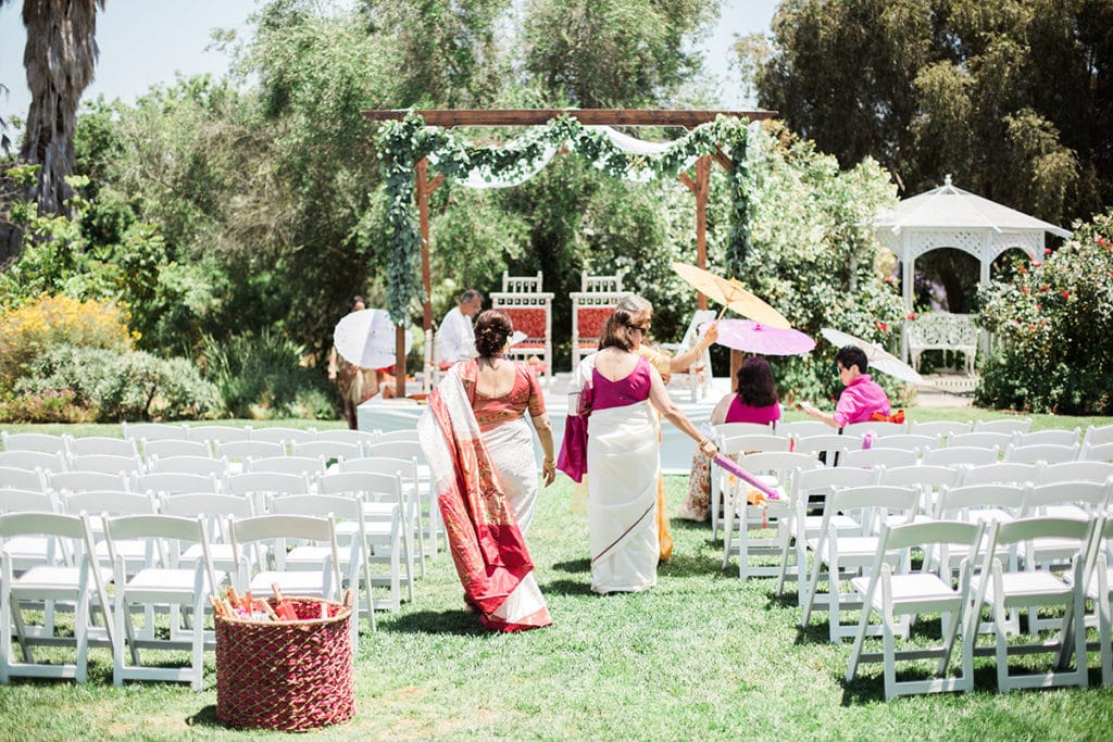 hindu ceremony mothers walking down aisle to mandap with simple green garland