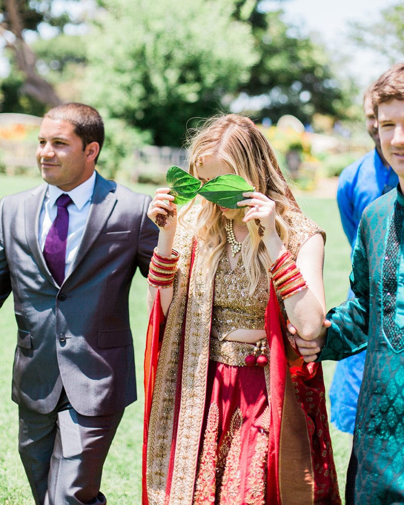 hindu ceremony with bride covering her eyes with leaves