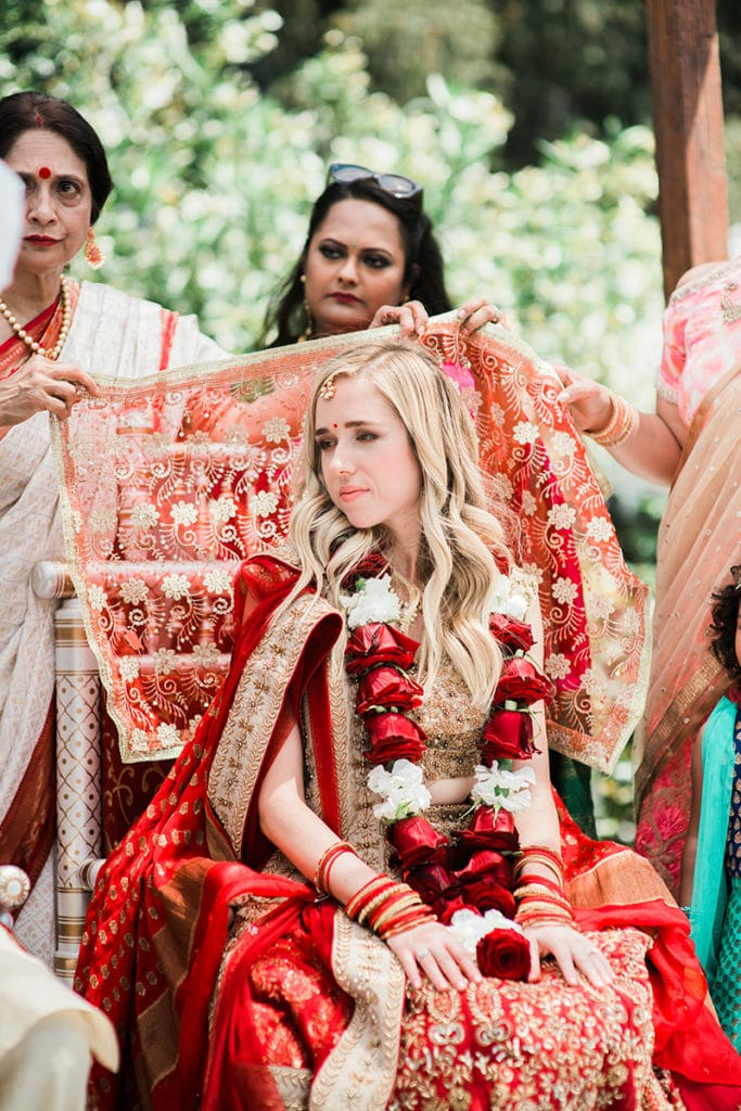 mothers and aunts cover bride during hindu ceremony