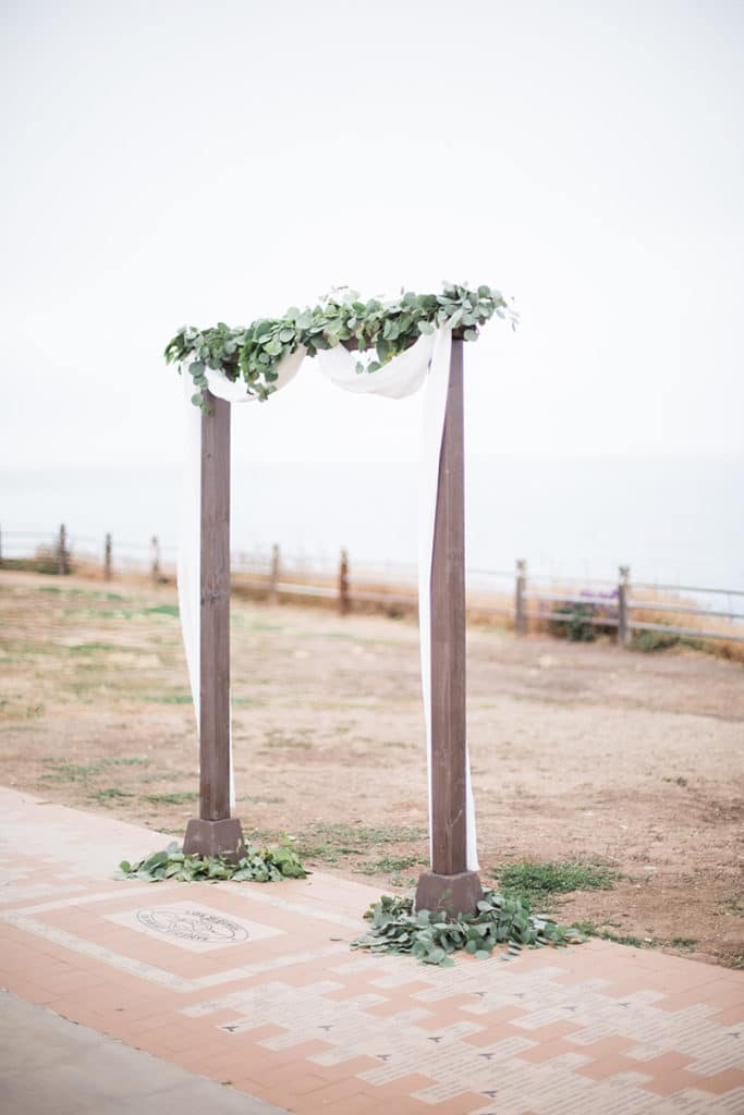 simple two post arch with fabric and garland for ocean side ceremony