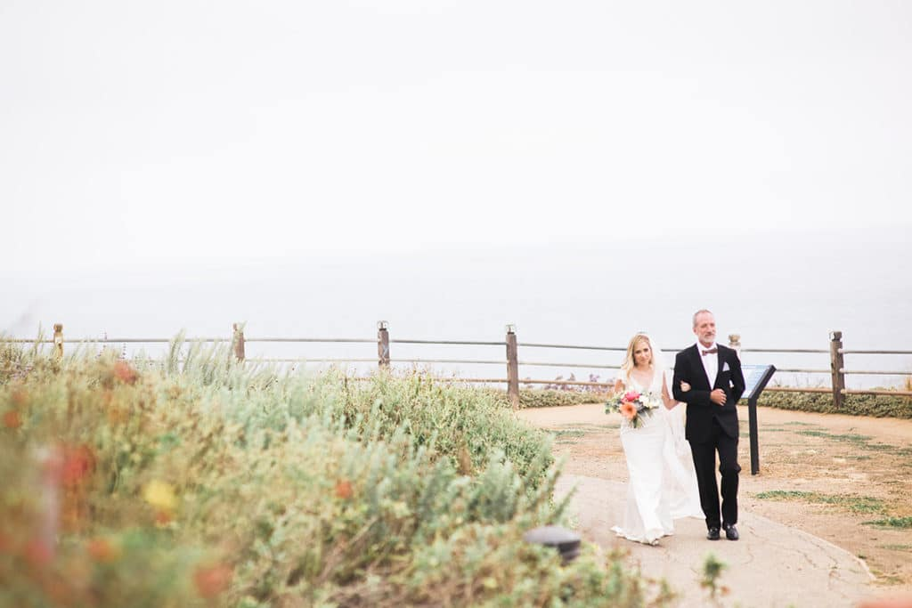 bride and father walk down aisle along the cliffs in palos verdes