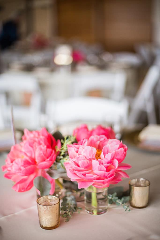 bright pink flowers on center of round table for wedding