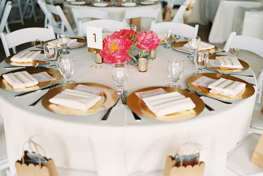 bright pink peonies and gold chargers on round tables with white linens