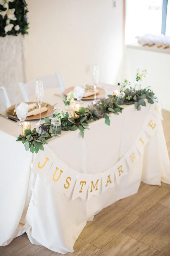 sweetheart table with green garland and gold plates