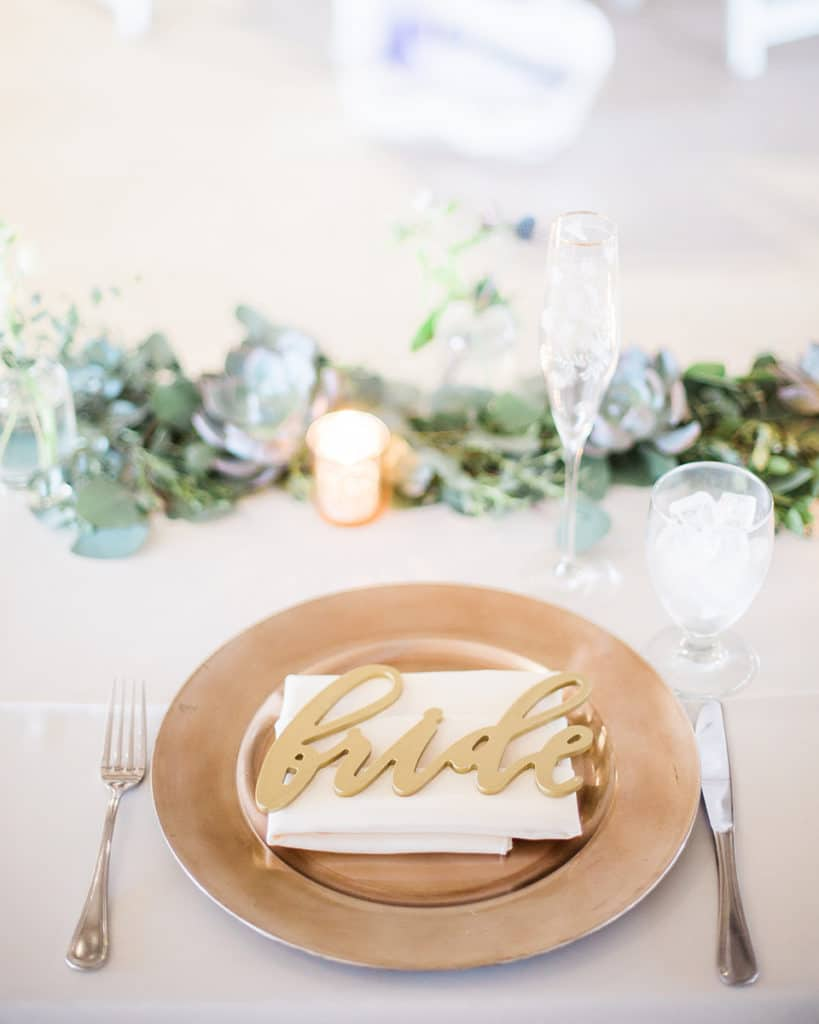 gold charger with ivory napkin and gold bride sign on sweetheart table