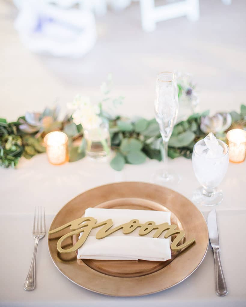 sweetheart table with ivory linen and napkin green garland and gold charger