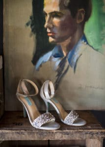bridal shoes in front of cool art piece