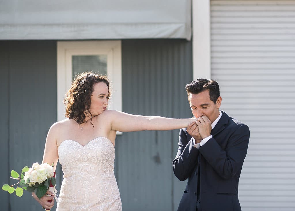Groom kisses bride on the hand in front of grey wall