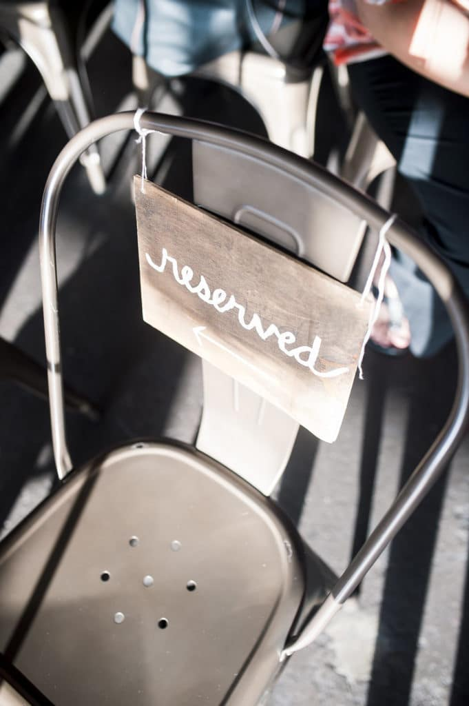 Wooden reserved sign on metal chair for ceremony