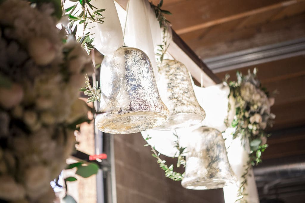 mercury glass bell hanging on ceremony arch