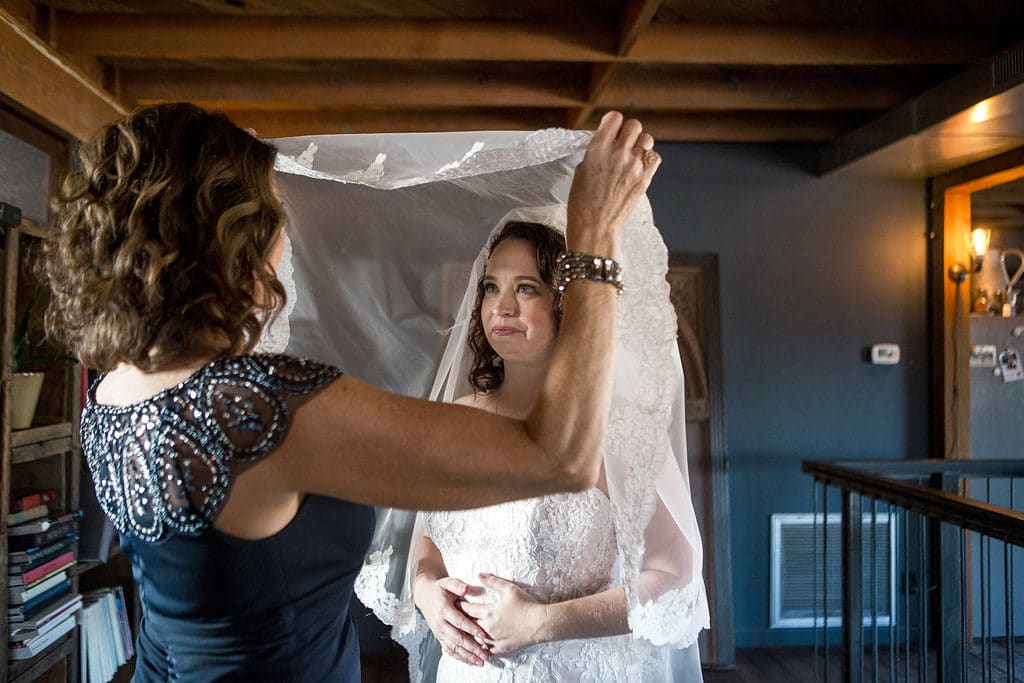 mother of bride puts veil on bride at smoky hollow studio