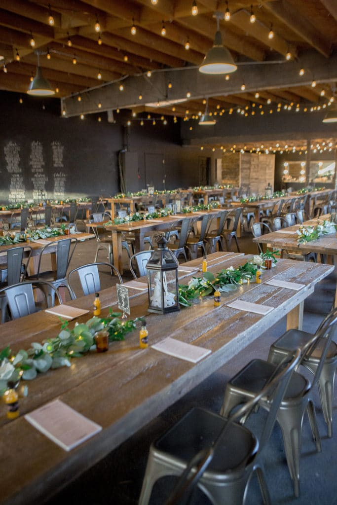 reception with garland candles and long wooden tables at smoky hollow studios