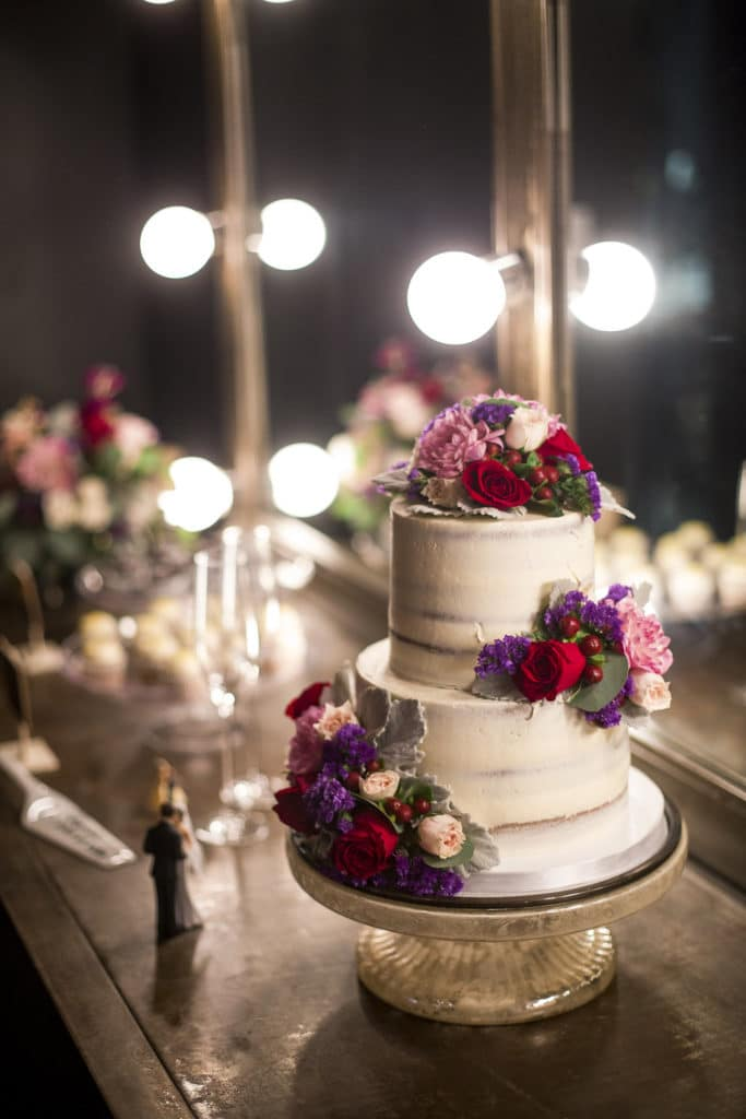 naked cake with pink and purple flowers at smoky hollow studios