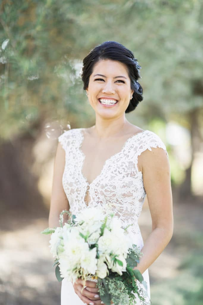 Lace detailing around neckline wedding gown. White and green bouquet for barn wedding
