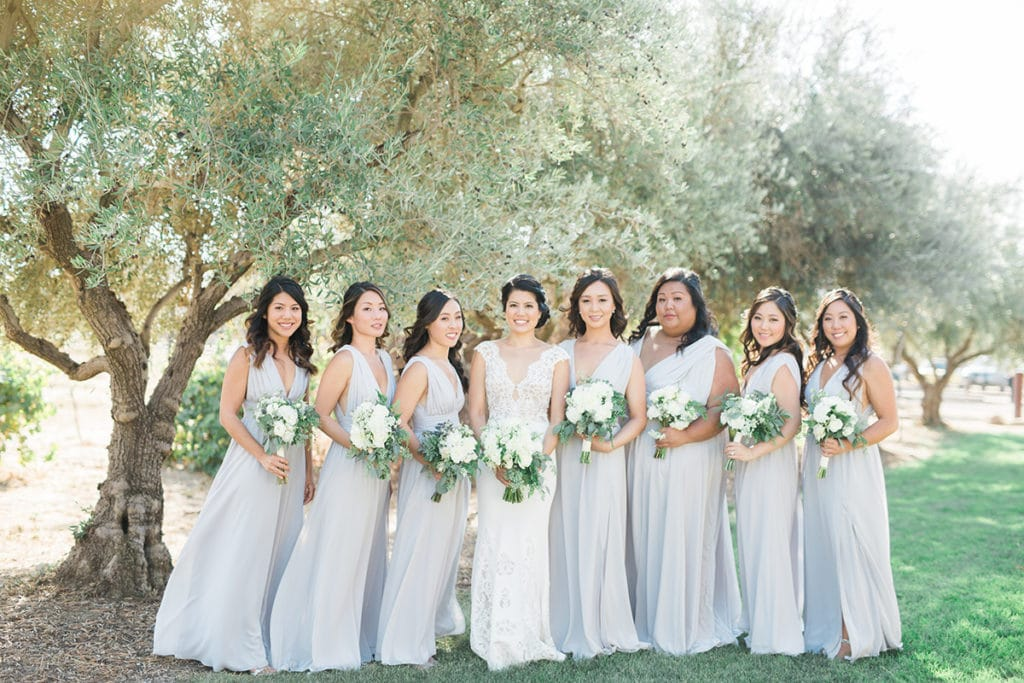 Bride and bridesmaids in soft lavender grey dresses at rustic barn wedding in San Luis Obispo