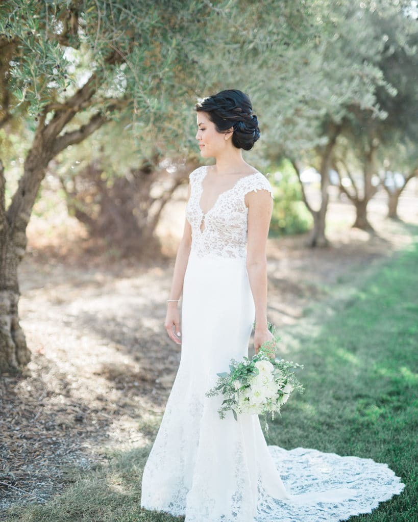 Bride with sleek dress and lace detailing outside the barn at the Santa Margarita Ranch