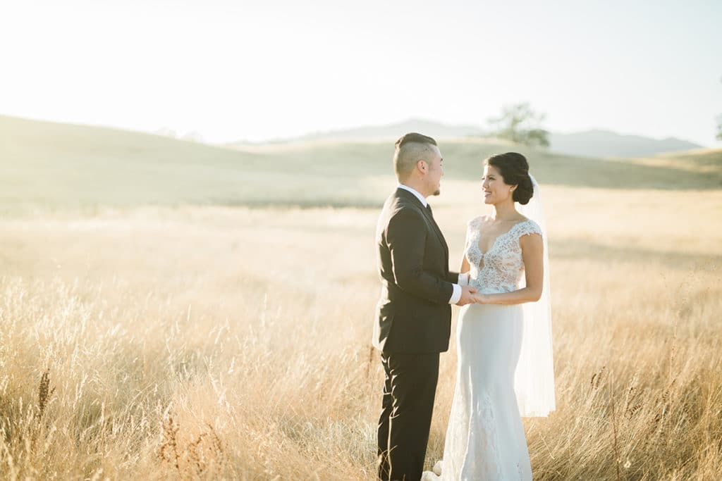 Bride and groom in field of golden when at sunset