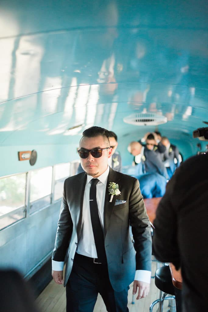 Groom and groomsmen in vintage school bus getting ready before wedding