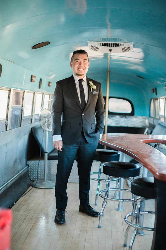 Groom in vintage school bus getting ready for wedding