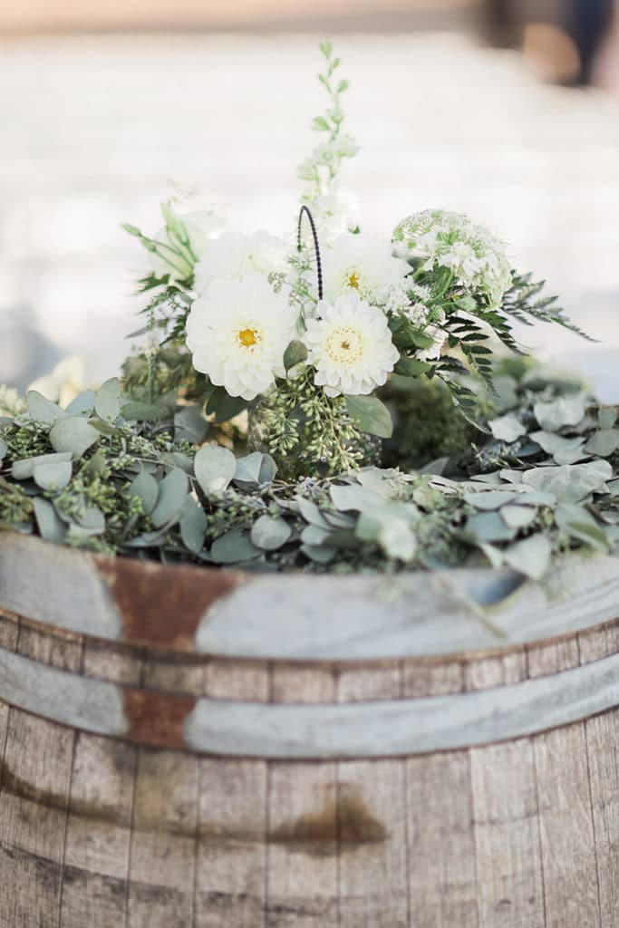 White flowers with greenery on vintage wine barrel for barn wedding