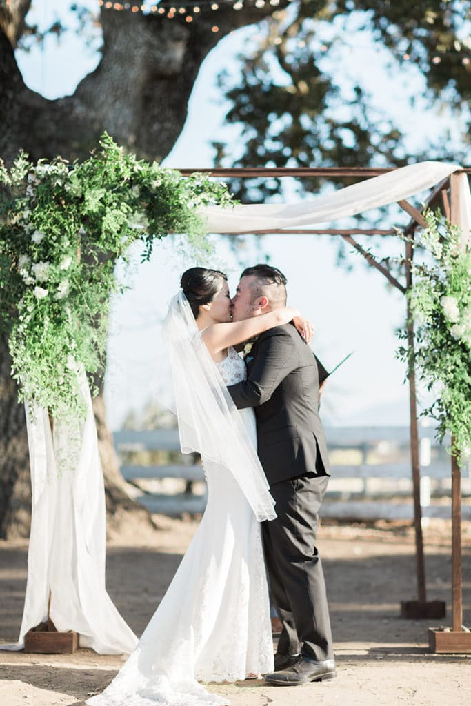 Bride and Groom kiss under a wooden chuppah with green garland and soft white fabric