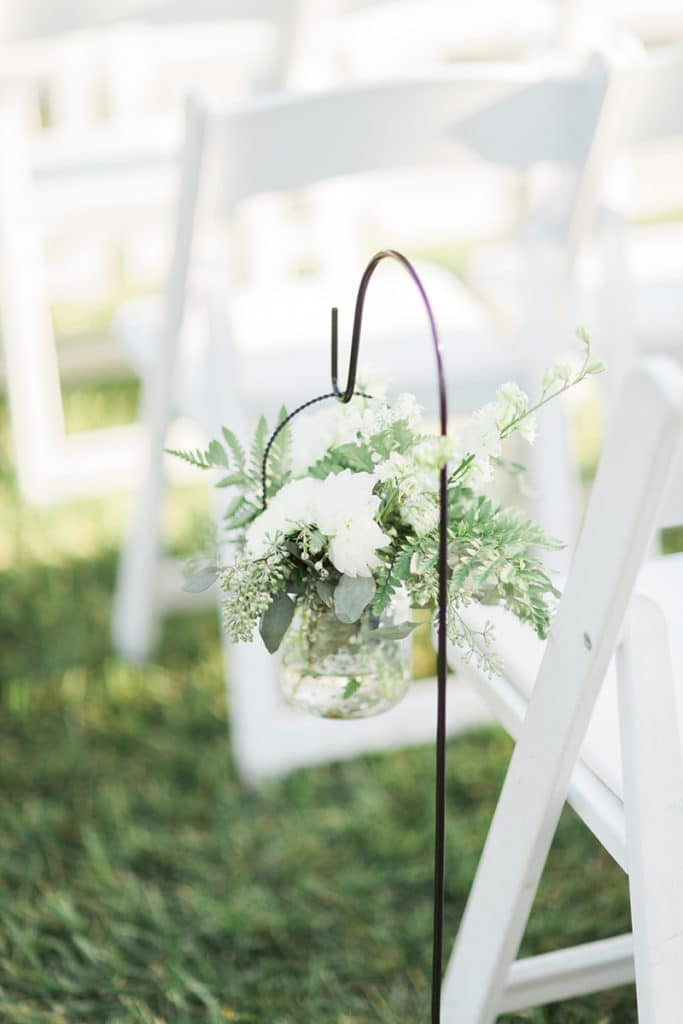 White flowers in glass jar on Shepard hooks down ceremony aisle